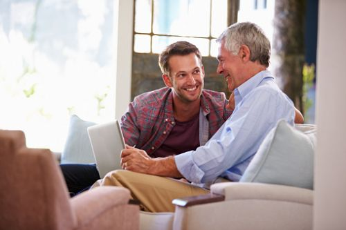 Senior Father Talking to Adult Son Successor Trustee on Couch