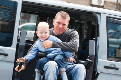 Disabled Man in Wheelchair with Son on Lap