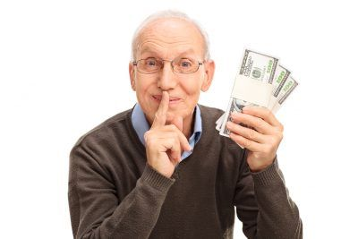 Senior gentleman holding three stacks of money and holding a finger on his lips isolated on white background