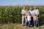 Three generations standing by cornfield on family farm