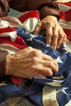 Old woman's hands on American flag